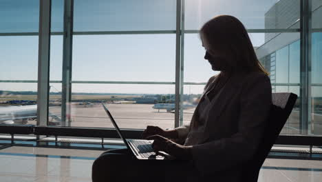 Silhouette-Of-A-Business-Woman-With-A-Laptop-Working-In-Anticipation-Of-Her-Flight-Sits-By-The-Large