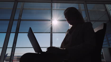 Silhouette-Of-A-Man-Using-A-Laptop-Near-A-Large-Window-In-The-Airport-Terminal