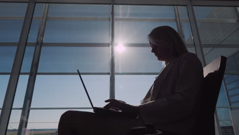 Silhouette-Of-A-Young-Business-Woman-Waiting-For-Her-Flight-In-The-Airport-Lobby-Using-A-Laptop
