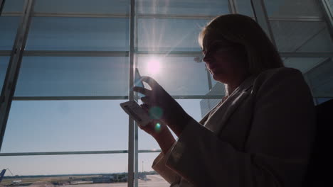 A-Passenger-With-A-Boarding-Pass-In-His-Hands-Is-Standing-At-A-Large-Window-Of-The-Airport-Terminal