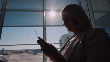 Young-Female-Passenger-Waiting-For-Flight-Looks-At-Boarding-Passes-Flight-Delay-Concept