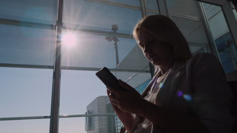 A-Woman-Is-Waiting-For-Her-Flight-At-The-Airport-Terminal-Using-A-Smartphone