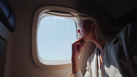 Business-Woman-With-Glasses-Flying-In-An-Airplane-Looking-Out-The-Window