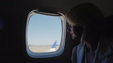 A-Young-Woman-Looks-Out-The-Window-Of-The-Plane-Which-Begins-To-Accelerate-Along-The-Runway-Start-Of