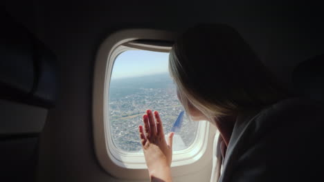 A-Female-Passenger-Looks-Out-The-Window-Of-The-Airliner-To-The-Ground-Below-Where-The-Big-Metropolis