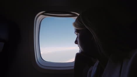 Silhouette-Of-A-Young-Woman-Flying-In-An-Airplane-Looking-Out-The-Window