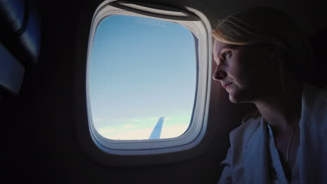 Lonely-Sad-Woman-Looks-Out-The-Porthole-Of-The-Plane