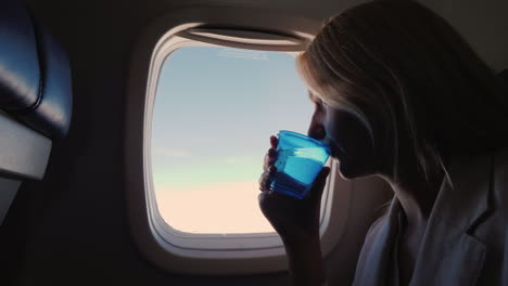 A-Female-Passenger-Airliner-Drinks-Water-From-A-Plastic-Cup