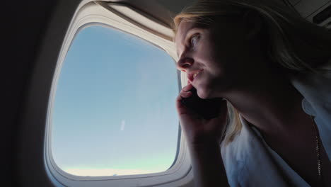 Business-Woman-Talking-On-The-Phone-In-The-Cabin-Of-An-Airliner