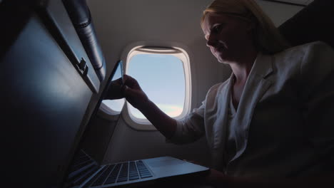 Woman-Opens-Laptop-In-The-Plane-Business-Trip-Concept