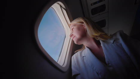 Young-Caucasian-Woman-Traveling-In-An-Airplane-Looking-Out-The-Window