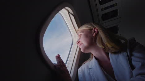 Successful-Young-Woman-Flying-In-An-Airplane-Looking-Out-The-Window-Low-Angle-Shot