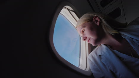 Low-Angle-Viev-Of-Woman-Flying-In-An-Airplane-Looking-Out-The-Window