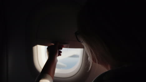 A-Woman-Opens-The-Porthole-Curtain-And-Looks-Out-The-Window-Of-The-Plane