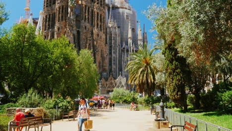 The-Famous-Sagrada-Familia-Church-In-Barcelona-Tourists-Walking-The-Camera-Moves-Toward-The-Temple