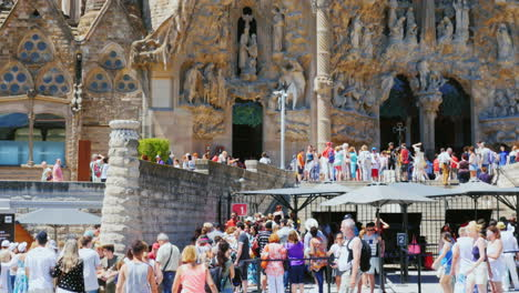 Many-Tourists-Walk-And-Take-Pictures-At-The-Entrance-To-The-Church-Of-The-Sagrada-Familia-In-Barcelo