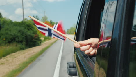 Hand-With-Norway-Flag-In-A-Car-Window-Travel-Scandinavia-Concept
