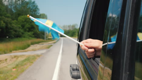 Hand-With-Sweden-Flag-In-A-Car-Window-Travel-Scandinavia-Concept