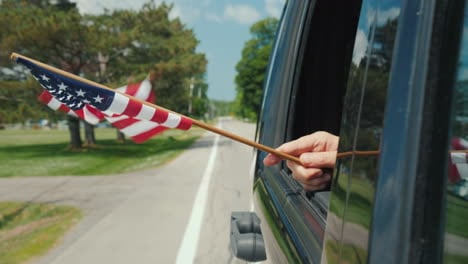 Hand-With-Usa-Flag-In-A-Car-Window-Travel-Scandinavia-Concept