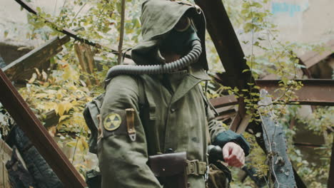 A-Man-Wearing-A-Gas-Mask-And-Protective-Suit-In-Abandoned-House-Looks-Readings-At-The-Wrist-The-Radi