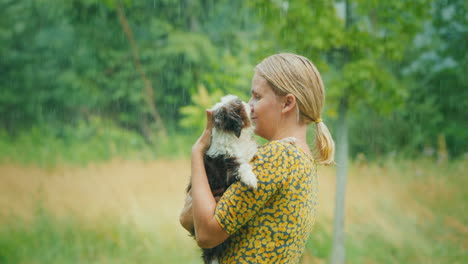Middle-Aged-Woman-With-A-Puppy-In-Her-Arms-Stands-In-The-Pouring-Summer-Rain-Unforgettable-Moments-O