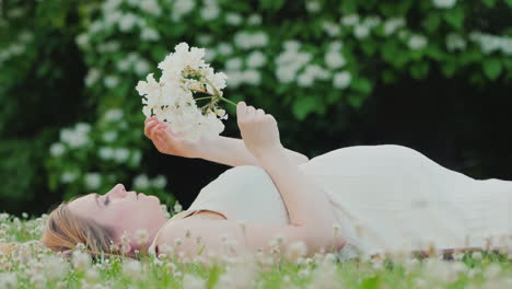 Attractive-Pregnant-Woman-Lying-On-The-Lawn-Holding-A-Flower