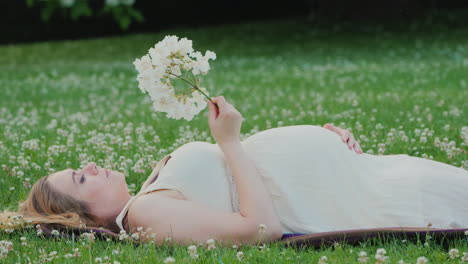 Cute-Pregnant-Woman-Lies-On-A-Lawn-Holds-A-Flower-In-Her-Hand-Dreams