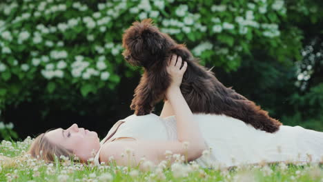 Active-Pregnant-Woman-Is-Playing-With-Her-Dog-In-The-Backyard-Of-The-House-Lying-On-The-Lawn