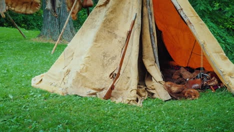 An-Old-Hunter-s-Tent-In-The-Forest-In-It-Lie-Animal-Skins-And-Weapons-American-Pioneers