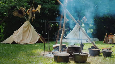 Native-American-Camp-In-The-Forest-Food-Is-Being-Prepared-In-The-Foreground-Traditional-Wigwam-Tents