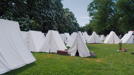An-Old-Military-Camp-Rows-Of-Tents-Stand-In-The-Forest-Reconstruction-Of-The-Times-Of-The-Wars-With-