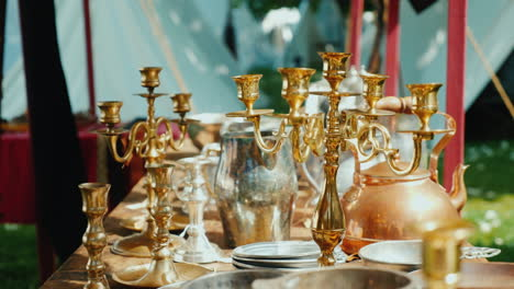 Antique-Dishes-Candlesticks-And-Other-Items-In-An-Antique-Outdoor-Tent