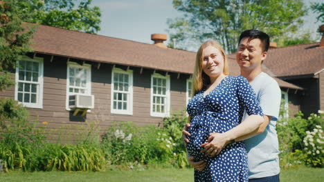 Happy-Young-Family-Near-Their-New-Home-Pregnant-Woman-And-Asian-Man