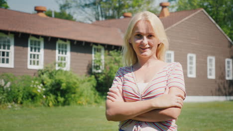 Portrait-Of-A-Caucasian-Woman-On-The-Background-Of-A-New-Country-House-Buying-A-Property