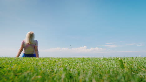 Woman-Relaxes-In-Nature-Sitting-In-A-Picturesque-Place-On-A-Green-Meadow