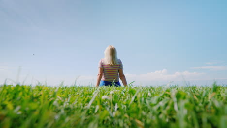 A-Woman-Is-Sitting-On-Perfect-Shorn-Grass-That-Goes-Into-A-Clear-Blue-Sky