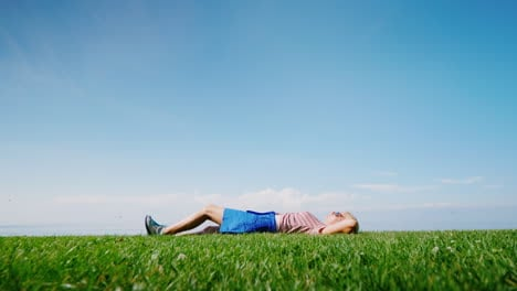 A-Happy-Woman-Lies-In-The-Middle-Of-A-Green-Meadow-Relaxes-And-Rests-In-Nature-Alone
