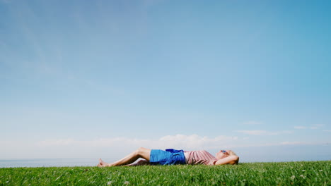 A-Young-Woman-Enjoys-Warmth-And-Summer-Lying-On-The-Green-Grass-Against-The-Blue-Sky