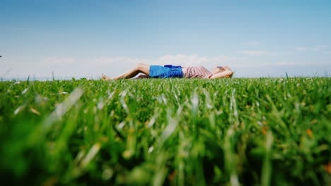 The-Green-Lawn-On-Which-The-Young-Woman-Lies-Looks-At-The-Sky-And-Has-A-Rest