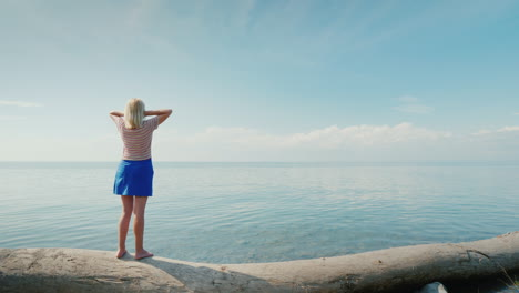 A-Young-Woman-Stands-On-A-Log-Admires-The-Beautiful-Landscape-Where-The-Sky-Merges-With-The-Sea