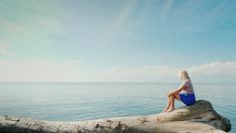 A-Young-Woman-Admires-The-Boundless-Sea-Which-Merges-With-The-Sky-Sits-On-A-Log-In-A-Picturesque-Pla