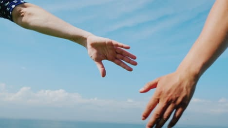 Young-Couple-Holds-Hands-Against-A-Blue-Sky