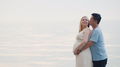 A-Young-Asian-Man-Hugs-His-Pregnant-Wife-On-A-Sunset-Background-Over-The-Sea-Multi-Ethnic-Couples-In