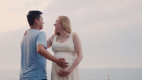 Happy-Young-Couple-By-The-Sea---Caucasian-Pregnant-Woman-And-Her-Asian-Husband