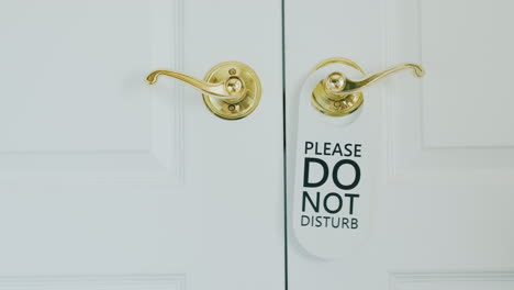 Honeymoon-In-A-Luxury-Hotel---Hand-Hangs-On-Do-Not-Disturb-Sign-On-A-Wooden-Door