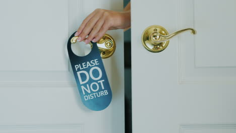 A-Female-Hand-Quickly-Hangs-A-Do-Not-Disturb-Sign-On-A-Door-Hand