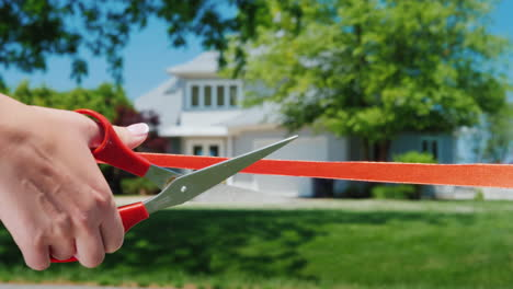A-Scissor-Cut-Arm-Cuts-A-Red-Ribbon-And-A-Typical-American-House-Is-Visible-In-The-Background-Housew