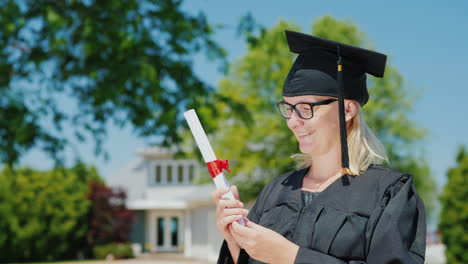 Portrait-Of-A-Woman-In-A-Mantle-And-Graduation-Cap-Holding-A-Diploma-In-Her-Hand-Against-The-Backgro