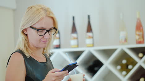 Young-Woman-In-Elegant-Black-Dress-Uses-A-Smartphone-In-The-Tasting-Room-Of-The-Winery