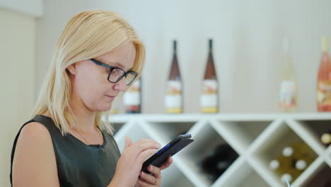 Portrait-Of-A-Young-Woman-In-Glasses-Uses-A-Smartphone-While-Waiting-For-Her-Order-In-A-Cafe